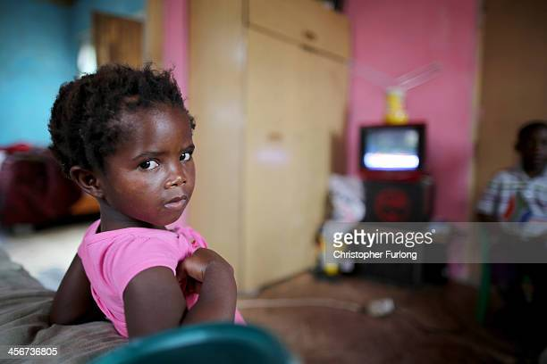 A young girl watches the televised funeral of former South African President Nelson Mandela in his home village of Qunu on December 15 2013 in Qunu...