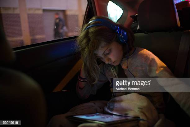 Young girl watching an iPad while in Car