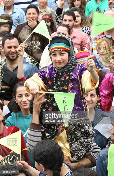 A young girl waves flags as Syriac Catholic Iraqis who fled the violence in their country gather to celebrate Palm Sunday that marks the triumphant...