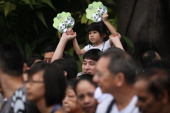 A young girl waves her panda claws in the air as she waits for the arrival of the refrigerated truck carrying the two giant pandas Kai Kai and Jia...