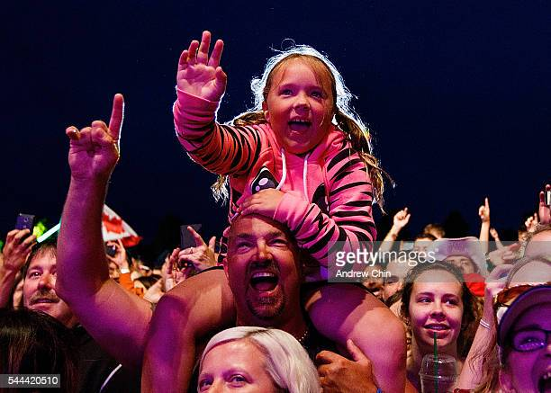A young girl waves to Canadian rock band Tom Cochrane and Red Rider performance onstage during Canada Day at Bill ReidÊMillennium Amphitheatre on...