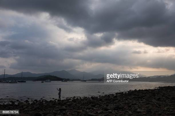 A young girl waves while searching for clams along the shore in Hong Kong on October 7 2017 / AFP PHOTO / DALE DE LA REY