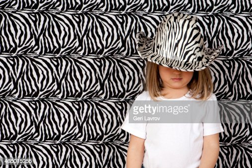 Young girl wearing a black and white striped hat