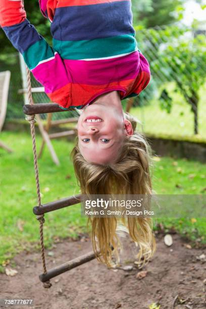 A young girl wearing a colourful shirt hangs upside down from a rope ladder outside on a summer day