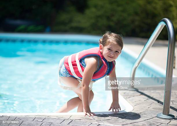 Young girl wearing a life vest at the pool