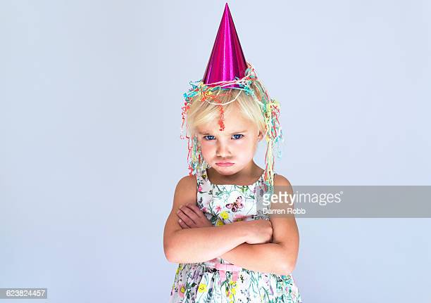 Young girl wearing a party hat looking sad