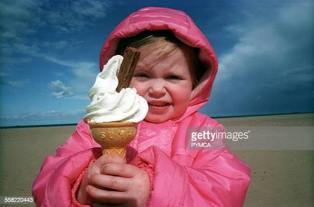 Young girl wearing a pink coat and holding an icecream on the beach UK 2003