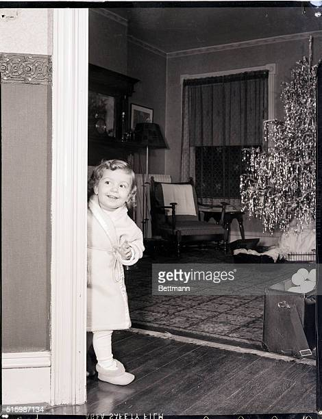 A young girl wearing a robe and slippers enters the family room at Christmas time A tree decorated with icicles stands in the background Undated...