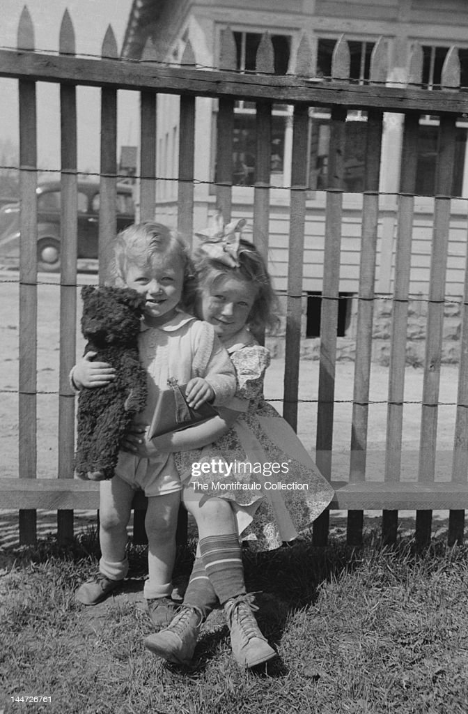 Young girl wearing a summer dress with a ribbon in her hair cuddling a younger child who is holding a Steiff type bear and small clutch bag with...