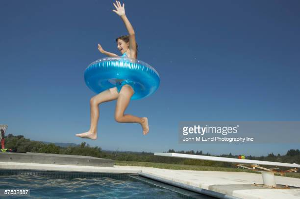 Young girl wearing an inner tube jumping off the diving board