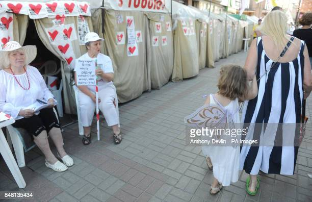 A young girl wearing angel wings passes demonstrators protesting against the imprisonment of opposition leader Yulia Tymoshenko near Independence...
