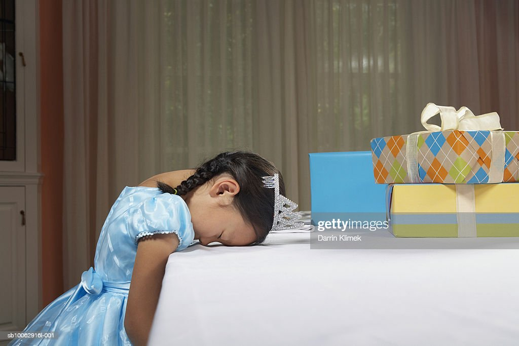 Young Girl Wearing Dress And Tiara Sleeping With Head On