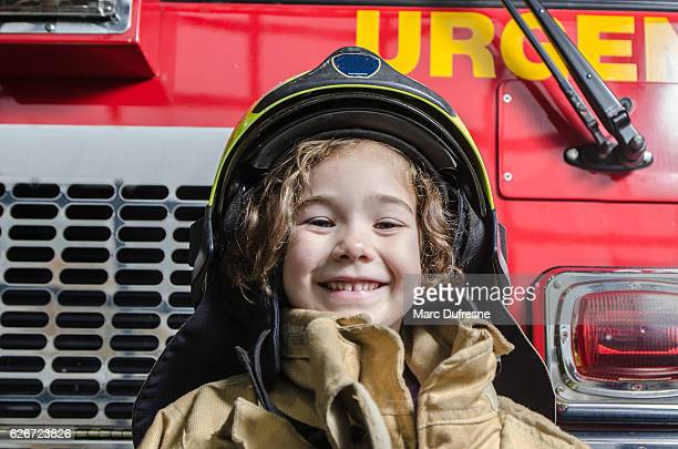Young girl wearing fireman coat and helmet
