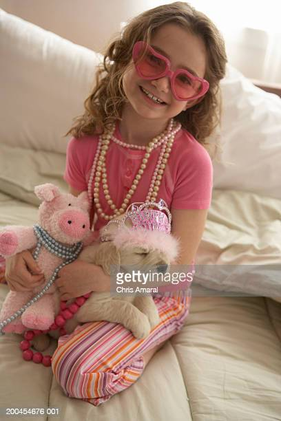 Young girl (8-10) wearing glasses on bed with dog, smiling