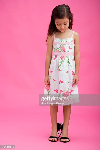 Young girl wearing high heel shoes, looking down