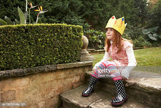 Young girl (6-7) wearing paper crown sitting in garden