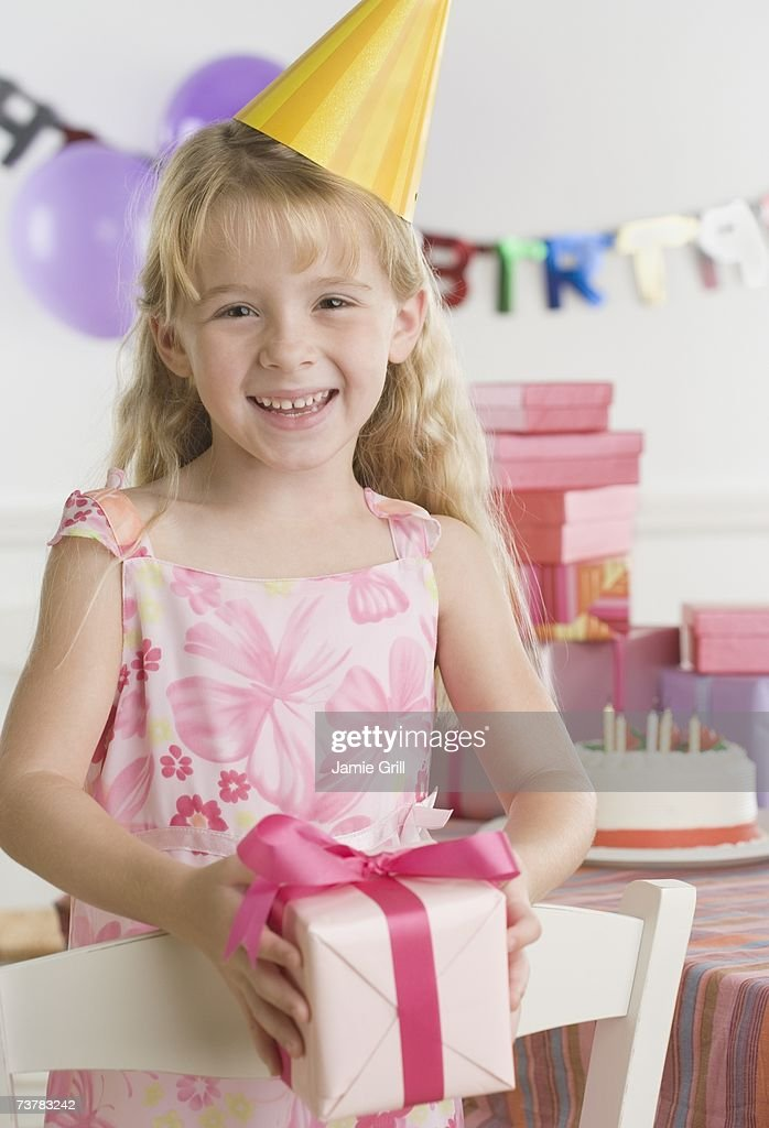 Young girl wearing party hat and holding gift : Stock Photo