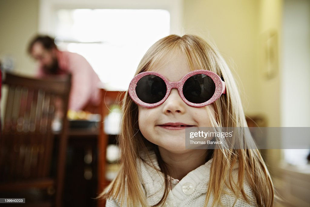 Young girl wearing pink sunglasses in home smiling : Stock Photo