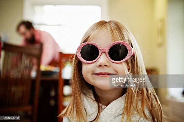 Young girl wearing pink sunglasses in home smiling
