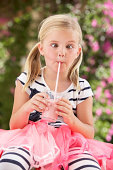 Young Girl Wearing Pink Wellington Boots Drinking Milkshake
