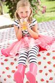 Young Girl Wearing Pink Wellington Boots Drinking Orange Juice