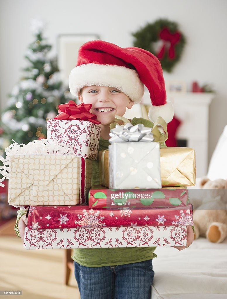 Young girl wearing Santa hat holding presents  : Stock Photo