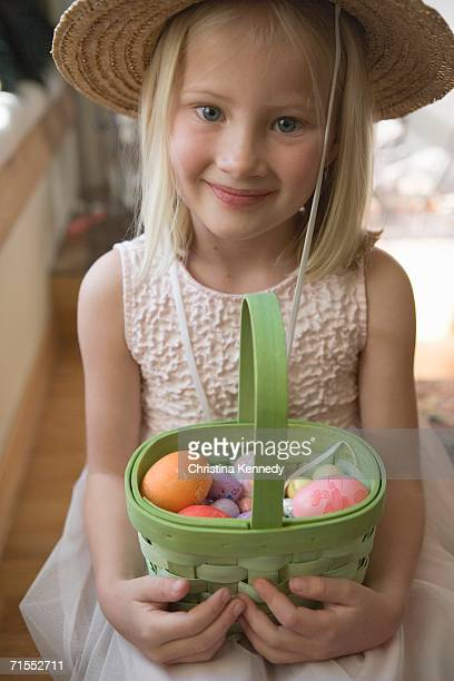 Young girl wearing straw hat and holding a basket of colorful Easter eggs