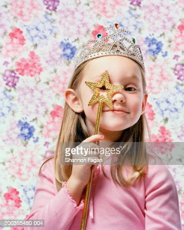 Young girl (4-6) wearing tiara and holding star, portrait