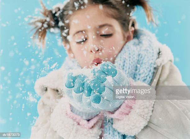 Young Girl Wearing Warm Clothing and Blowing a Handful of Snow
