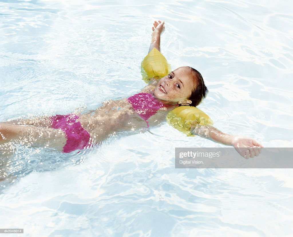 Swimming Pool Wings : Young girl wearing water wings floating on in a