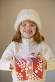 Young girl wearing winter hat and holding gift