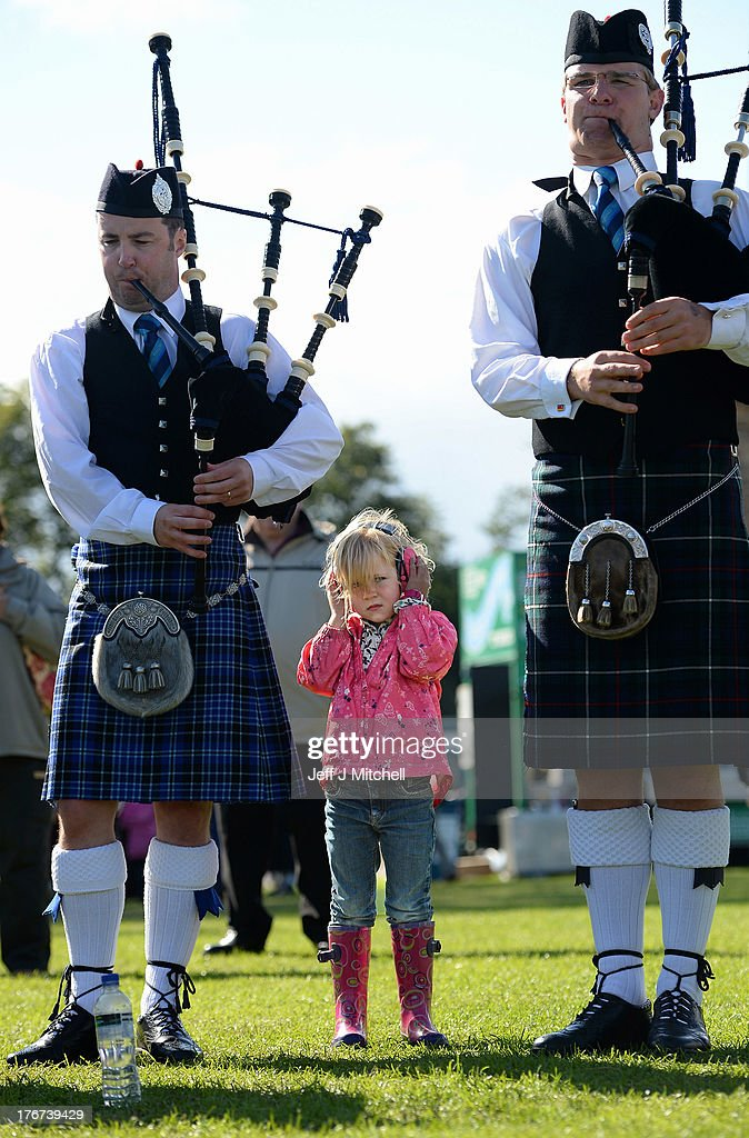 A young girl wears ear defenders as a pipe band takes part in 2013 World Pipe Band Championships at Glasgow Green on August 18, 2013 in Glasgow, Scotland. The annual World Pipe Band Championships has returned to Glasgow this weekend, with 225 pipe bands competing for the title.