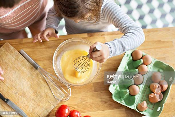 Young girl whipping eggs in a bow
