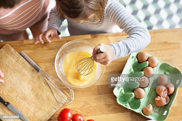 Junges Mädchen peitschendem Eier in einer Schleife