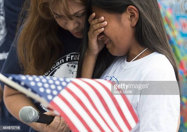 A young girl whose father was deported protest cries during a protest in response to US President Barack Obama's delay on immigration reform in front...