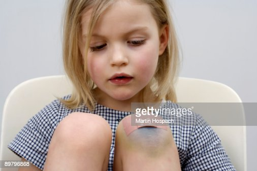 A young girl with a adhesive bandage on her knee