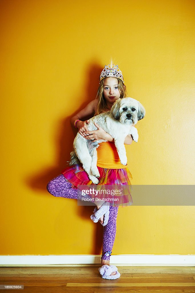 A young girl with a dog in tree pose. : Stock Photo