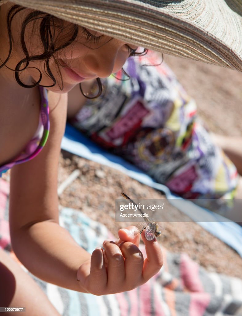 A young girl with a dragonfly on her finger : Stock Photo