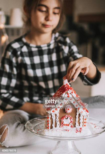 Young girl with a gingerbread house at Christmas time
