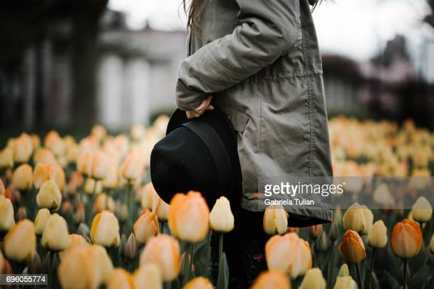 Young girl with a hat in tulips garden at cold spring day