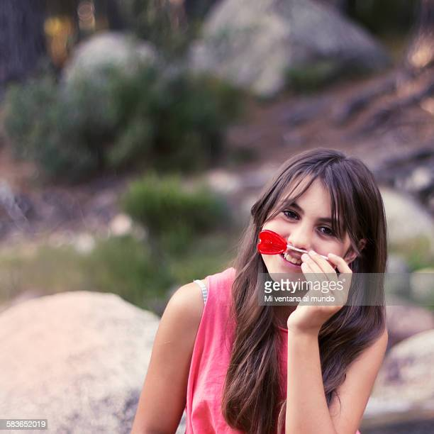 Young girl with a heart shaped lollipop