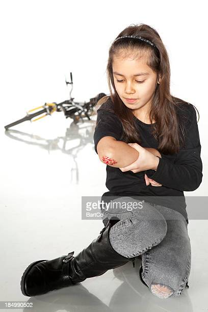 Young girl with a painful elbow on white