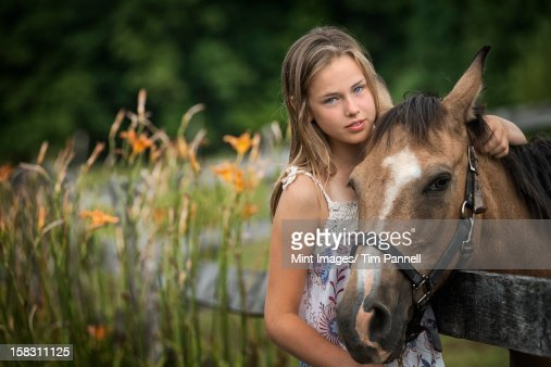 A young girl with a pony wearing a halter, in a field full of wild flowers and grasses. : Stock Photo