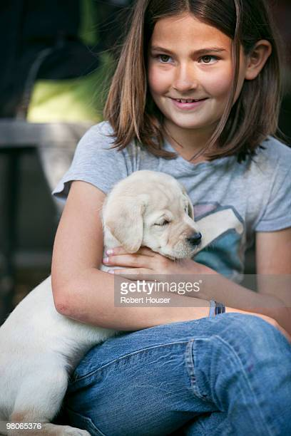 Young girl with a white labrador puppy.
