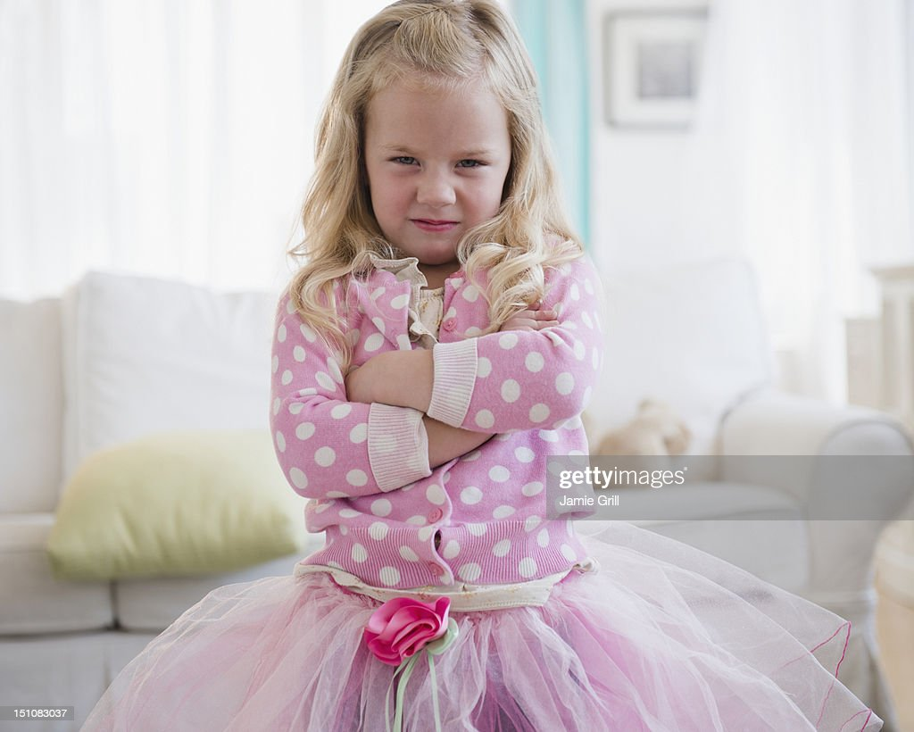 Young girl with arms crossed, unhappy : Stock Photo