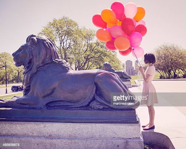 Young girl with balloons bouquet in a city park.