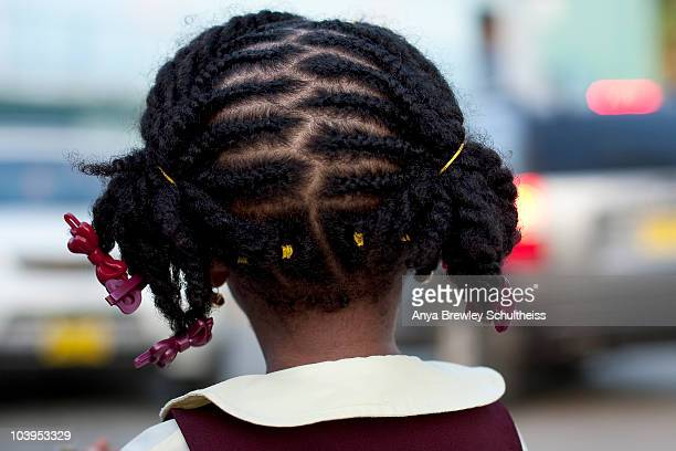 Young girl with braided hair looking away.