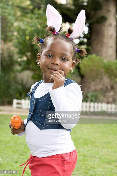 Young girl with bunny ears holding Easter egg, South Africa
