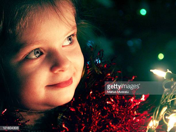 Young girl with christmas lights in her hand