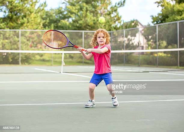 Young Girl With Curly Red Hair Playing Tennis